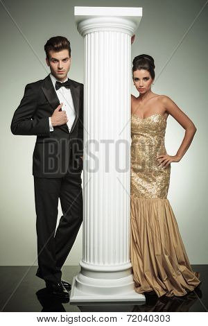 formal man and woman in evening clothes posing near column in studio