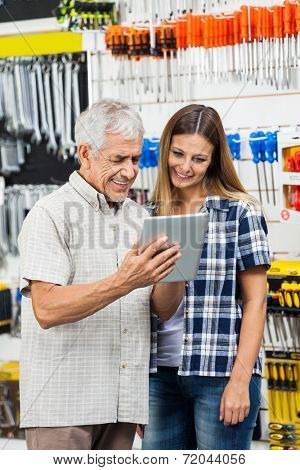 Happy father and daughter using tablet computer while standing in hardware shop