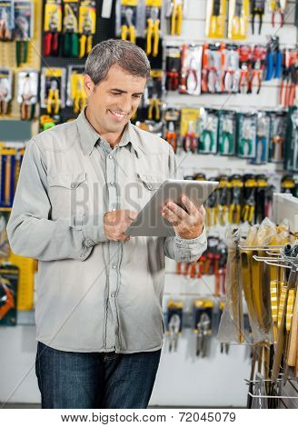 Mature male customer man using tablet computer in hardware store
