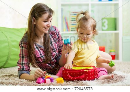 Happy Mother And Kid Play At Home
