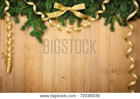 Christmas background with firtree, bow and ribbons on wood - horizontal