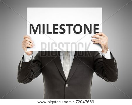 A business man holding a paper in front of his face with the text milestone