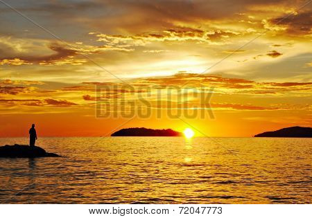 Silhouette Of A Man Standing On Rock Edge During A Beautiful Sunset