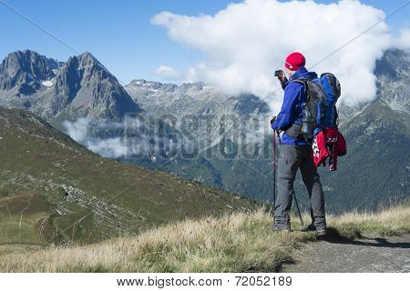 COL DE BALME, FRANCE - SEPTEMBER 01: Backpacker photographing view with Aiguille de Loriaz in the background. The area is a stage of the popular Mont Blanc tour. September 01, 2014 in Col de Balme.
