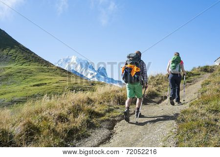 COL DE BALME, FRANCE - SEPTEMBER 01: Backpackers walking on trail with Mont Blanc in the background. The area is a stage of the popular Mont Blanc tour. September 01, 2014 in Col de Balme.