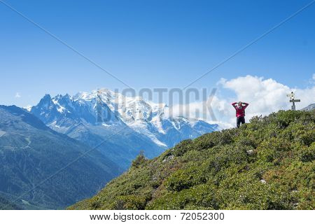 COL DE BALME, FRANCE - SEPTEMBER 01: Backpacker stretching and looking at view with Mont Blanc in the background. The area is a stage of the Mont Blanc tour. September 01, 2014 in Col de Balme.
