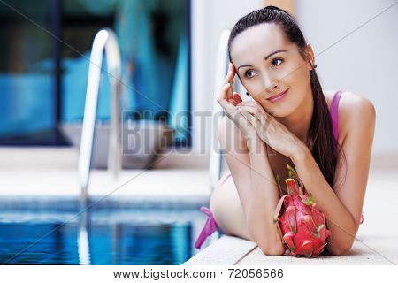 beautiful slim woman by the swimming pool with a dragon fruit