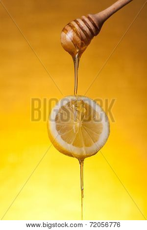 Honey flowing on lemon slice, studio shot over yellow background