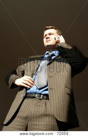Businessman With Cellular Phone Is Staring Into The Sun