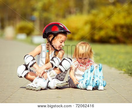 two little sisters in a roller skates and  helmet sitting  on the street