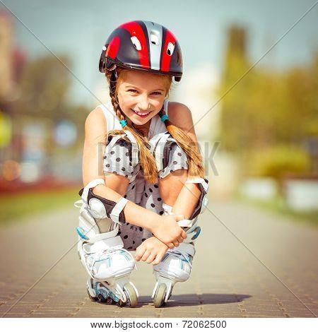 Little girl in roller skates sitting on a city street