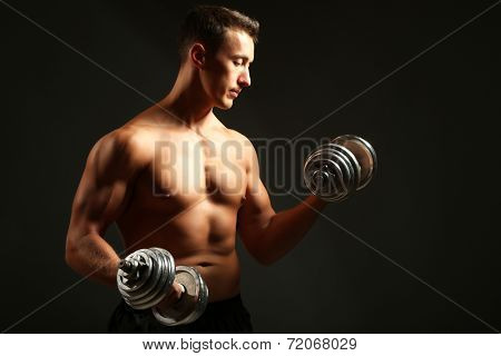 Handsome young muscular sportsman execute exercise with dumbbells on dark background