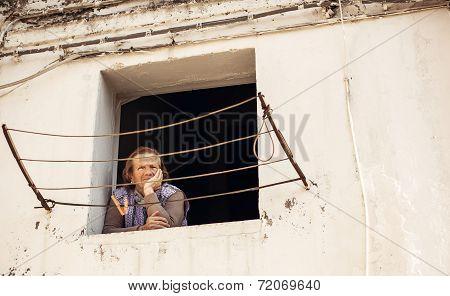Senior woman looking through window in Bari