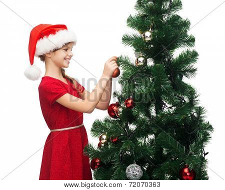 christmas, x-mas, winter, happiness concept - smiling girl in santa helper hat decorating a tree