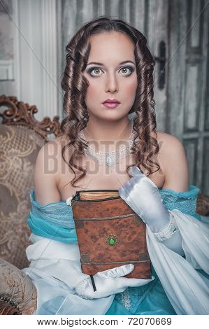 Beautiful Woman In Medieval Dress On The Armchair
