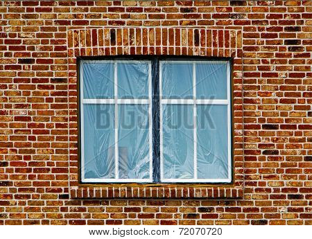 Window Under The Plastic Film In Brick Wall