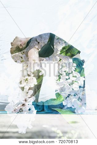 Double exposure portrait of attractive woman performing yoga asana combined with photograph of lilac flowers.