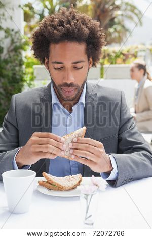 Businessman having sandwich for lunch outside at the coffee shop