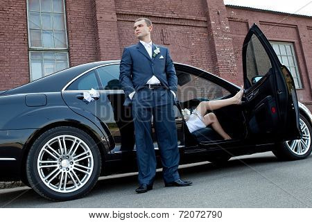 Wedding ceremony. Groom next to an executive car which sits bride.