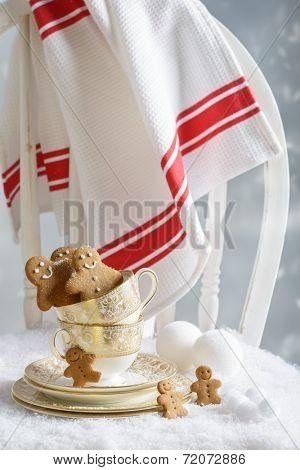 Freshly baked gingerbread men sitting in vintage teacups on festive chair