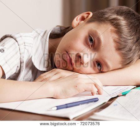 Sad boy doing homework. Crying boy.