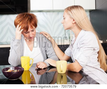 Daughter soothes sad mother. Young woman calm mature woman