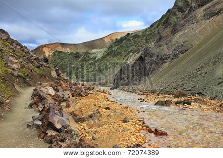 Steep mountain slopes, the path and the creek in the gorge. National Park Landmannalaugar in Iceland