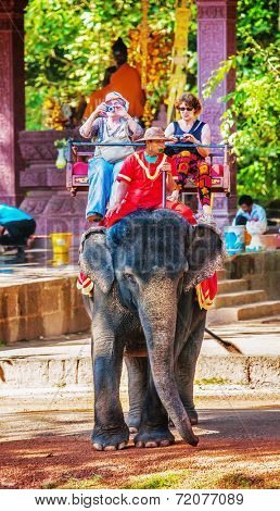 SIEM REAP, CAMBODIA - NOVEMBER 16, 2011:  unidentified tourists ride an elephant between ruins at Angkor in Siem Reap, Cambodia. Angkor temples and ruins are UNESCO World Heritage Site.