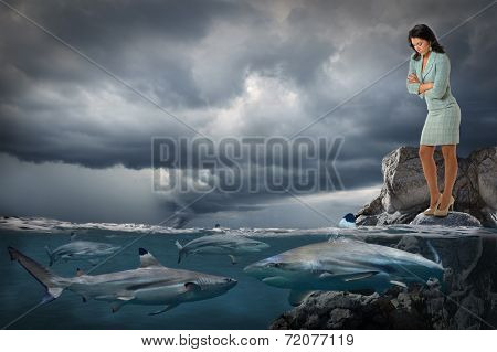 Competitive business concept with businesswoman looking at sharks swimming in ocean