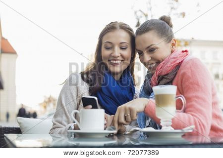 Happy female friends using cell phone at sidewalk cafe