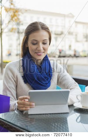 Young woman using tablet PC at sidewalk cafe