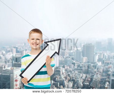 advertising, direction and childhood concept - smiling little boy with white blank arrow pointing right over city background