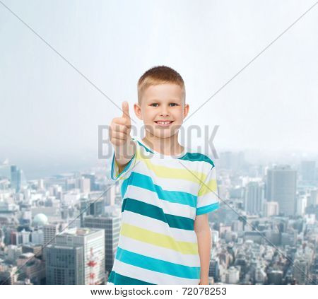 happiness, childhood and people concept - smiling little boy in casual clothes showing thumbs up over city background