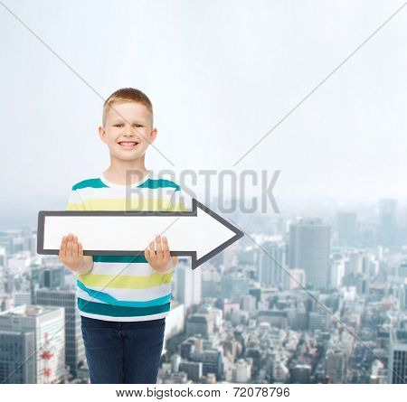 advertising, direction and childhood concept - smiling little boy with white blank arrow pointing up over city background