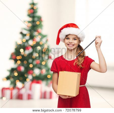 christmas, x-mas, winter, happiness concept - smiling girl in santa helper hat with gift box and magic wand