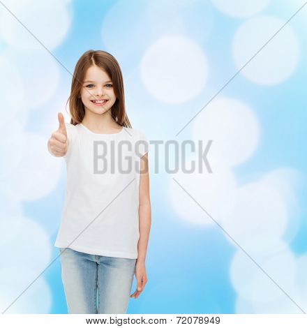 advertising, childhood and people - smiling little girl in white blank t-shirt showing thumbs up gesture over blue background