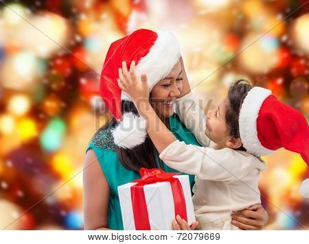 christmas, holidays, celebration, family and people concept - happy mother and child girl in santa helper hats with gift box over red lights background
