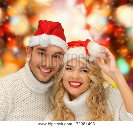 winter, holidays, christmas and people concept - smiling couple in sweaters and santa helper hats over red lights background