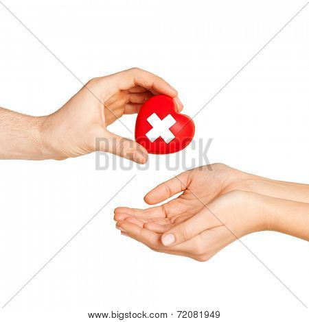 healthcare, charity and medicine concept - doctor hand giving heart with red cross symbol to patient