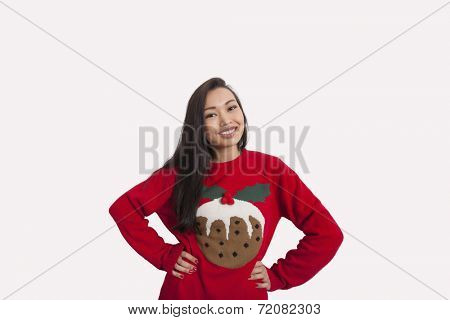 Portrait of woman in Christmas sweater standing with hands on hips over gray background