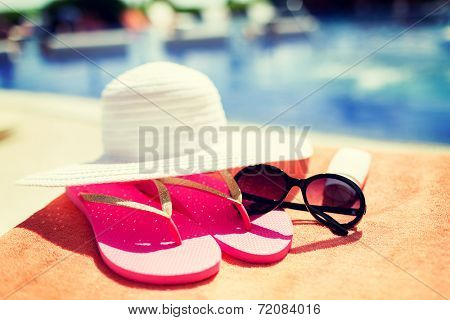 beach, summer, vacation and accessories concept - close up of hat, sunscreen and sunglasses at pool