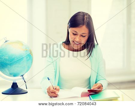 education and school, travel concept - female teacher with globe and notepad