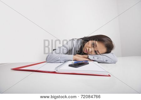 Exhausted businesswoman leaning at office desk