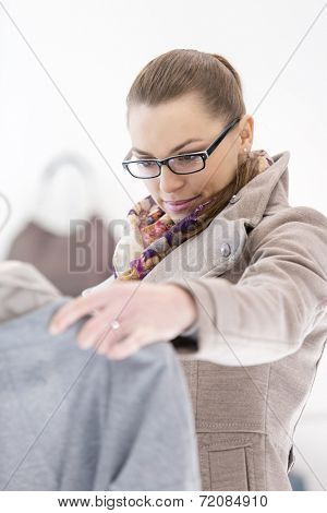 Young woman analyzing sweater in store