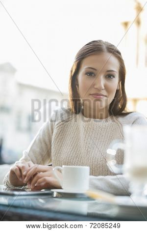 Portrait of young woman at sidewalk cafe