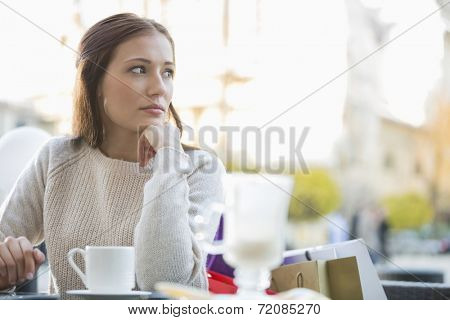 Young woman looking away while sitting at sidewalk cafe