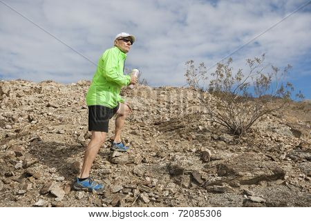 Side view of senior man holding water bottle while standing on mountain