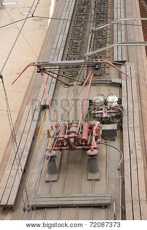 A view from above of an electric train with a red contact electrical supply network in Russia