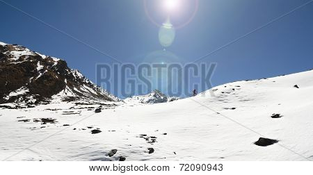 Alpinisht Climbing Mountains Through Deep Snow Under Bright Sun