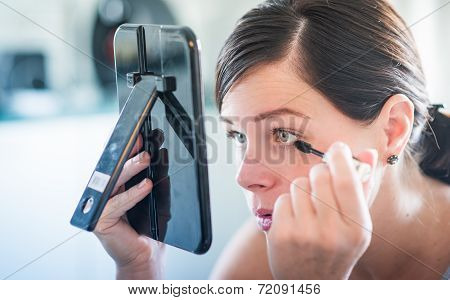 young wonderful woman applying her beautiful makeup in a mirror